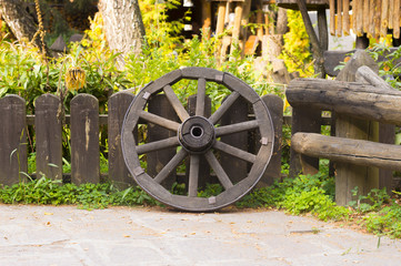Vintage Wooden Wheel at Background of Ancient Fence