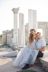 Beautiful young couple,the groom and the bride,blond hair,cute smile at the lovers,the bride sits on the lap of the groom on the background of ancient stone architecture in the summer outdoors