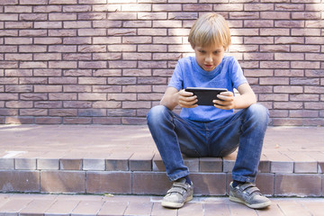 Child with mobile phone sitting outdoors. Boy looks at the screen, use application, plays. Sunny day. Brick wall building background. people, technology, leisure concept