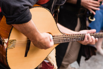 street musician playing the mandolin through the streets of a city