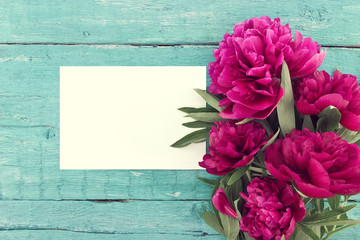 Red peony flowers on turquoise rustic wooden background