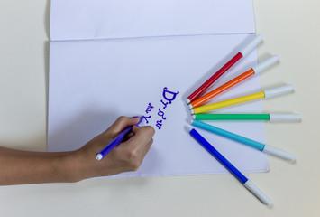 Ребенок рисует фломастерами на белой бумаге. Концепция образования, хобби, развлечение.