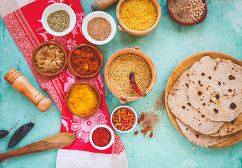 Middle east food concept , spices, bio, organic cereals in ceramic bowls with vintage spoon over on a azure backdrop with homemade arabian bread.