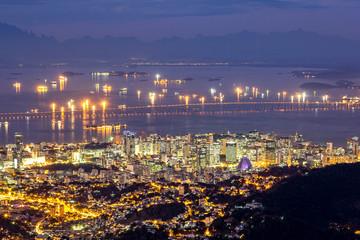 Fototapete - Aerial view of Rio de Janeiro downtown by night. Rio-Niteroi Bridge spans Guanabara Bay