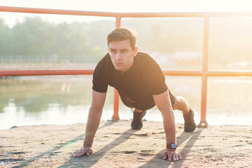 Fit man doing warm up exercise before start his workout training.