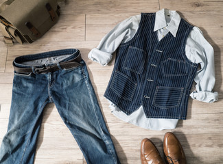 Top view - Vintage male clothing ( Shirt , Navy vest , jeans )and accessories on the wooden background