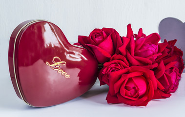 Valentine composition with red roses and red gift box in form of heart isolated on a white background