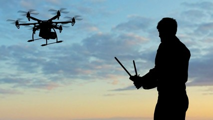 Man operating a drone at sunset using a controller