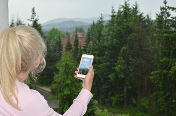 Blonde lady looking at cloudy landscape and her cell phone screen with a picture of the same landscape on nice weath