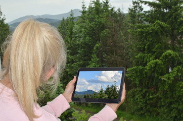 Blonde woman looking at cloudy landscape and her tablet white screen with a picture of the same landscape on nice weather