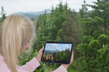 Blonde lady looking at cloudy landscape and her tablet white screen with a picture of the same landscape on nice weather