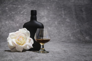 Black, White and Amber color on a rose, black brandy bottle and snifter