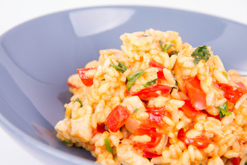 Risotto with chicken, tomatoes, bell pepper, onion, parsley and garlic on a blue plate on a wooden background