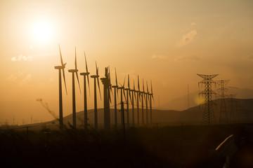 Windkraftanlage im Gegenlicht mit Strommast