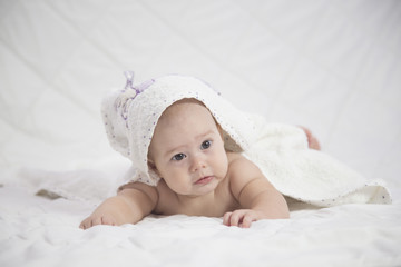 Adorable girl baby, looking out under a white blanket/towel