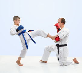 With black belt trainer teaches the athlete to beat kick leg on the simulator