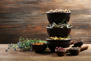 Natural flower and herb selection in  bowls on wooden background