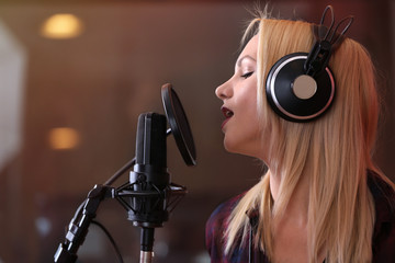 Young woman recording a song in a professional studio