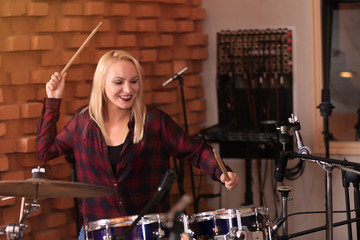 Woman playing drums in a recording studio