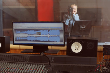 Young woman recording a song in a professional studio. View from sound engineer workplace