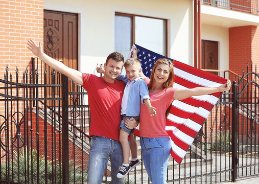 Happy family with American flag in the yard
