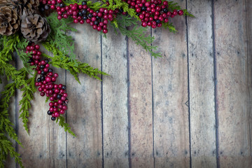Christmas Garland with Pine Cones and Berries on a wood plank bo