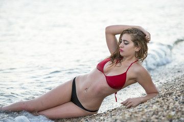 Blond woman with desired curved body wear two pieces bikini, ocean as background. Photo taken late afternoon