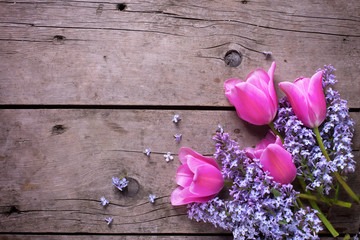Background with  lilac  and pink tulips flowers on vintage woode
