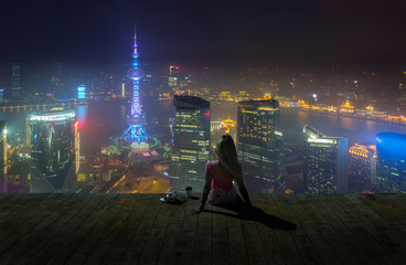 Woman sitting on the roof with coffee cup and enjoing view on night Shanghai.