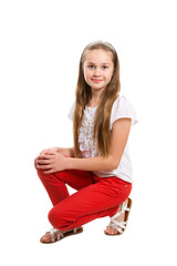 An eleven years girl is sitting in studio, isolated on white background