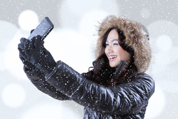 Girl in warm clothes taking selfie picture