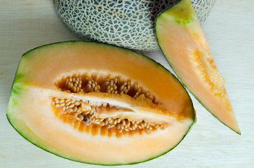 Cantaloupe or Charentais melon with half and seeds on wooden boa