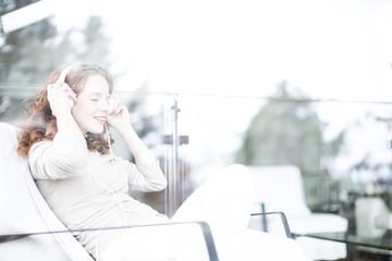 Frau zu hause aus der Couch hört Musik, Hörbuch