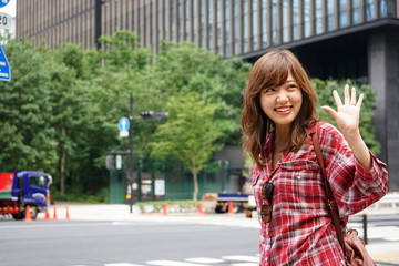 Young Japanese woman saying good-bye to her friend on the street