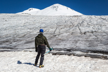 Mountaineer man in crampons and helmet with ice axe looking to Elbrus mountains summits. Group of mountaineers on a background. Active lifestyle, freedom, success concept.