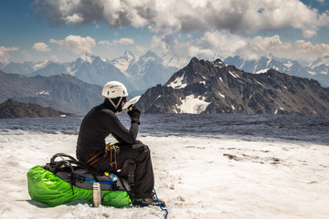 Mountaineer man sitting on a backpack, keeping a cup in hands and having a rest. Ice field and snowy mountains on background. Active lifestyle, freedom and extreme vacation concept.