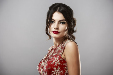 Portrait of a beautiful young woman in red dress.