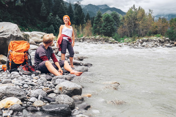 Two tourists refresh near the mountain river