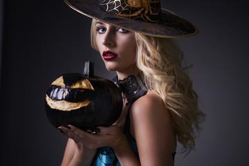 Sexy witch holding dark pumpkin.
