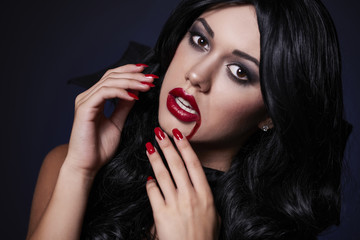 Sexy vampire with blood on the lips