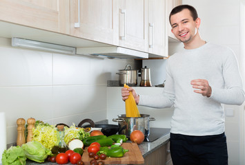 Portrait of smiling male cooking pasta