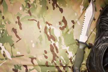 Combat knife and shoes on military camouflage fabric background