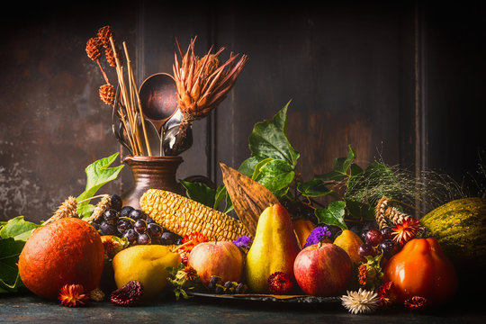 Various fall fruits and vegetables on dark rustic kitchen table at wooden background, side view,copy space. Autumn harvest concept.