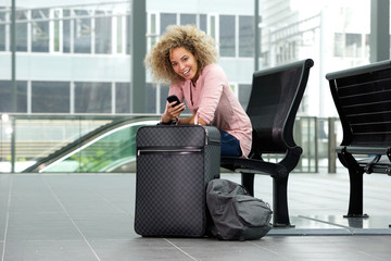 Smiling female traveler sitting with suitcase and cellphone