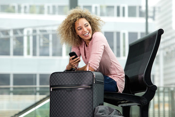 Smiling woman with cellphone and luggage
