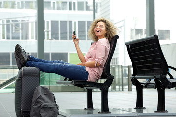 Laughing traveler sitting with feet on suitcase