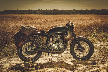 The vintage custom cafe racer in a field.