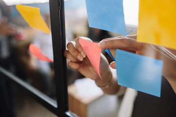 Hands of woman sticking adhesive notes on glass Wall mural
