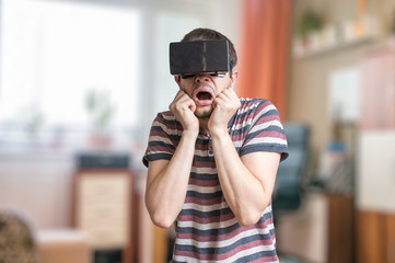 Man is wearing 3D virtual reality headset and is scared of something.
