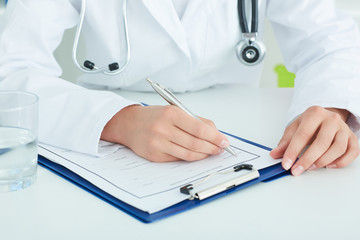 Physician working with paper in hospital office room.